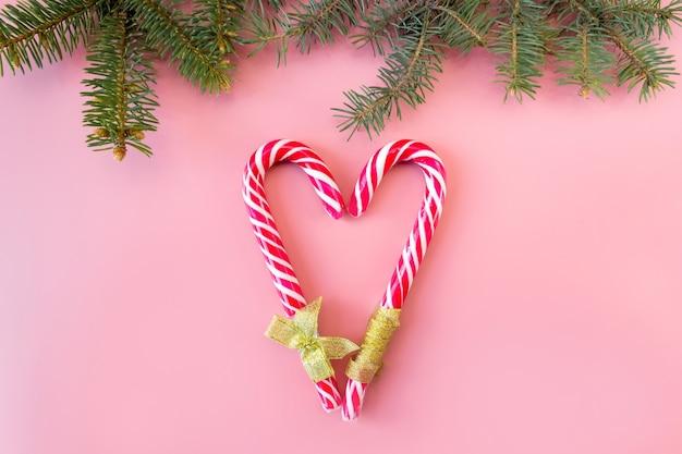 Laski karmelowe w formie serca ze świerkowymi gałązkami na różowym tle, płasko świecki, widok z góry.