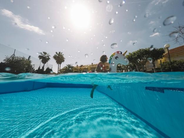 Lata i basenu pojęcie z kobietą na nadmuchiwanej jednorożec