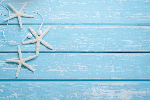 Lata morza tła rozgwiazda i hełmofony na błękitnym drewnianym tle.