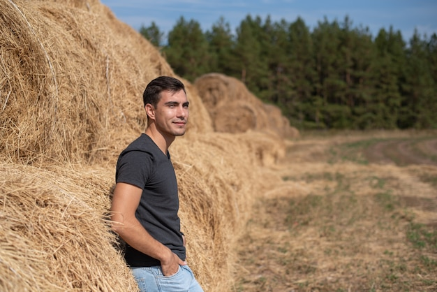 Łata portret uśmiechniętego rolnika w szarej koszulce stoi plecami do siana wygląda na polu, sianokosy, żniwa, koncepcja przemysłu