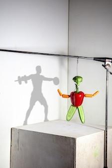 Latająca kompozycja jedzenia tworząca piękny sportowiec rysujący cień na ścianie