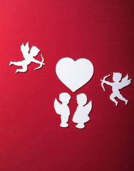 Latająca sylwetka kupidyna, dwa białe anioły, szczęśliwe banery walentynkowe, styl sztuki papieru. amour na czerwonym papierze