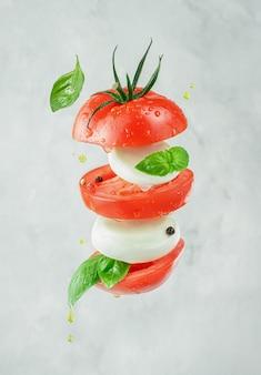 Latająca włoska sałatka caprese z mozzarellą, pomidorami i bazylią na szarym tle.