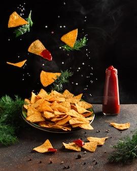 Latające chipsy kukurydziane z pieprzem i solą na talerzu z butelką ketchupu na ciemnym tle