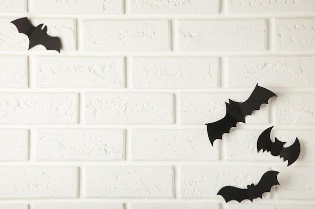 Latające czarne nietoperze na białej ścianie