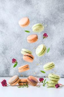 Latające francuskie macaroons i kwiaty na szarym tle. koncepcja lewitacji żywności.