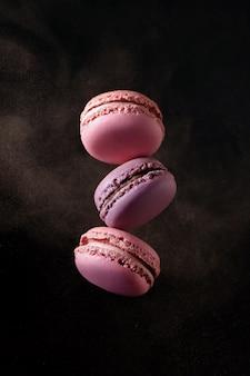 Latające francuskie różowe i fioletowe makaroniki z proszkiem kakaowym