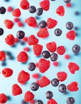 Latające jagody na niebieskim stole. spadające owoce malin i jagód