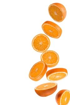 Latające owoce. spadać pokrojona pomarańczowa owoc odizolowywająca na bielu