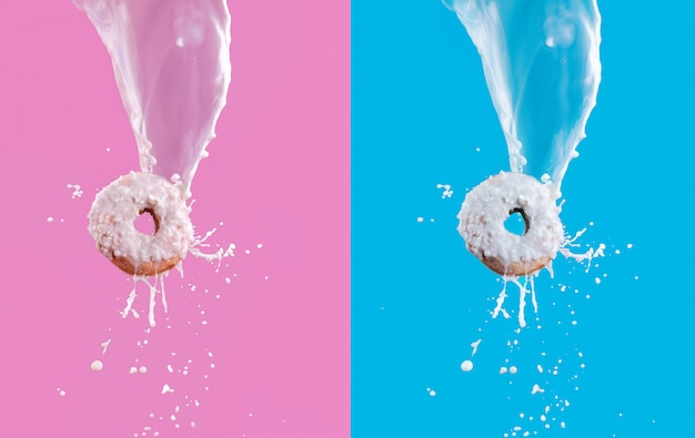 Latające pączki z białą czekoladą szkliwione i rozpryskiwania mleka na różowym i niebieskim tle. koncepcja słodkiego jedzenia