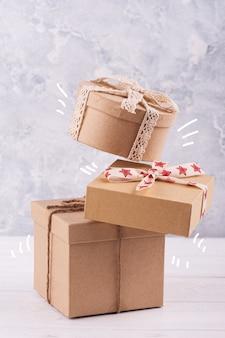Latające pudełka na prezenty kraft na białym stole.