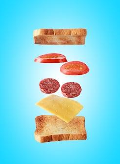 Latające warstwy kanapki z grzankami, salami, serem i warzywami na niebieskim tle. koncepcja żywności śniadaniowej