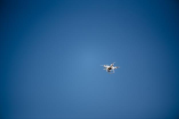Latający dron quadcoptera na czystym, błękitnym niebie
