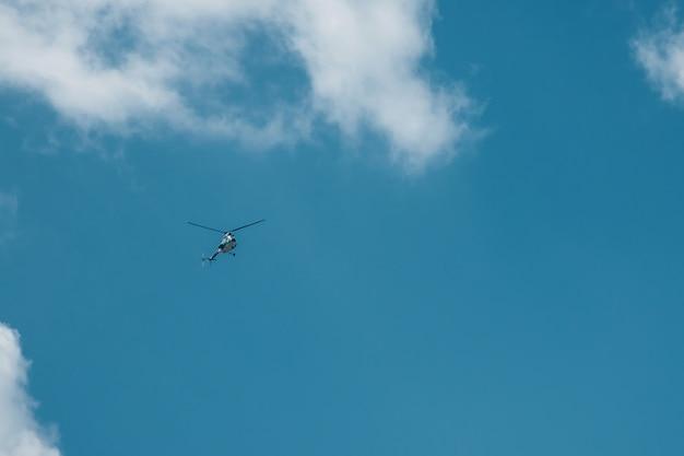 Latający mały helikopter wysoko w błękitnym chmurnym niebie.