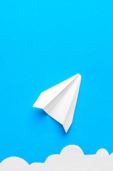 Latający papierowy samolot w chmurach na błękitnym tle. pojęcie lotu, podróży, transferu