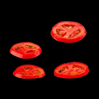 Latający pomidor. plasterki pomidora czerwony na czarnym tle. warzywo levity unoszące się w powietrzu.