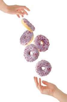 Latający purpurowy pączek między żeńskimi rękami odizolowywać na bielu. koncepcja lewitacji żywności.