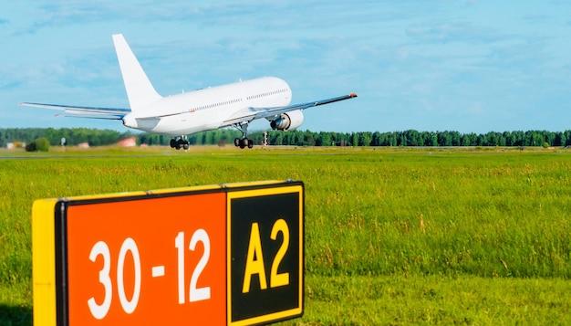Latający samolot na lotnisku na pierwszym planie płyta z pasem startowym