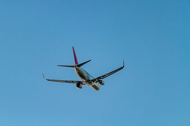 Latający samolot pasażerski na niebieskiego nieba surfce