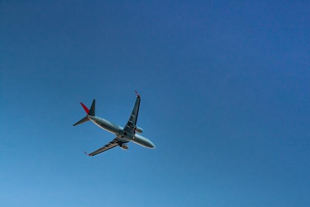 Latający samolot pasażerski na niebieskim niebie