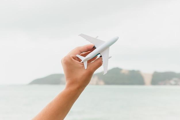 Latający samolot zabawkowy, przedstawiający plażę i niebo, reprezentujący podróże i turystykę, z miejscem na reklamy i teksty. pokazuje morro do careca w tle, w rio grande do norte