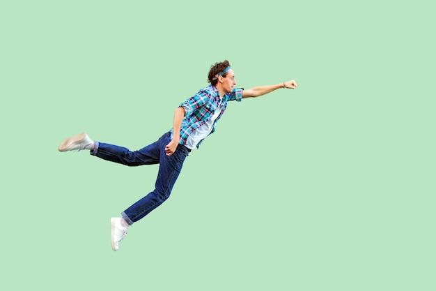 Latający superman. koncepcja entuzjazmu. widok z boku na całej długości młodego człowieka w stylu casual czuł się superbohaterem lub super człowiekiem i latał. kryty strzał studio, na białym tle na zielonym tle.