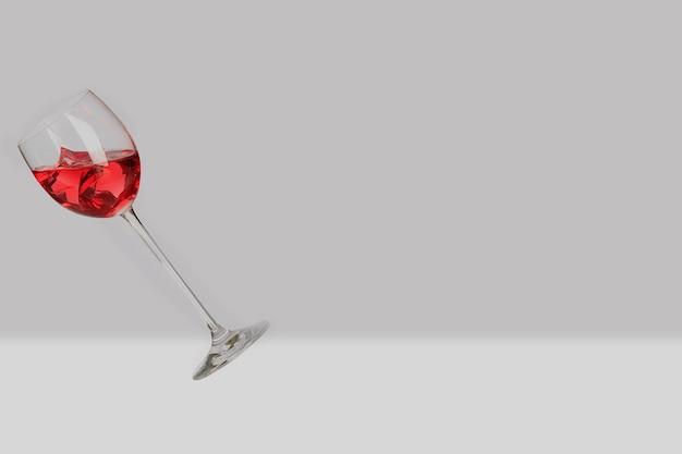 Latający szklany kubek z czerwonym winem i lodem