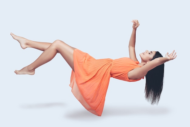 Latanie tak wysoko. pełnej długości strzał studio atrakcyjnej młodej kobiety w pomarańczowej sukience, unoszącej się w powietrzu i trzymającej zamknięte oczy