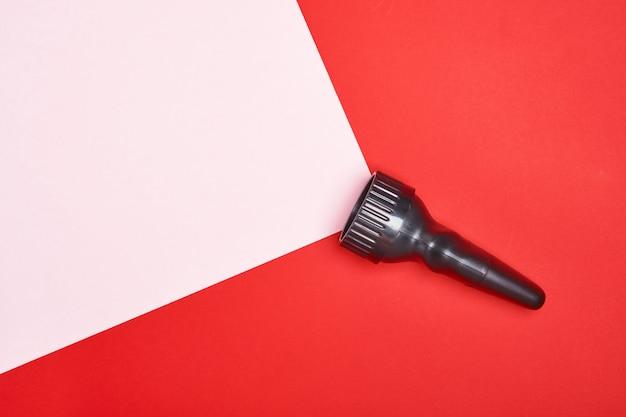Latarka na czerwonym tle z różowym promieniem światła, wykonana z miejsca na kopię papieru. widok z góry