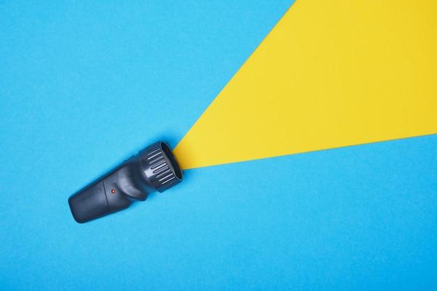 Latarka na niebieskim tle z żółtym promieniem światła, wykonana z miejsca na kopię papieru. widok z góry