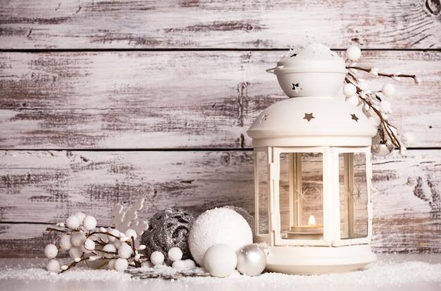 Latarnia cristmas z dekoracjami i śniegiem na białym odrapanym drewnianym tle