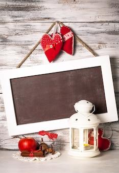 Latarnia cristmas z tablicą na pozdrowienia nad odrapaną drewnianą ścianą