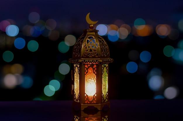 Latarnia, która ma symbol księżyca na górze z nocnym niebem i jasnym tłem bokeh miasta.