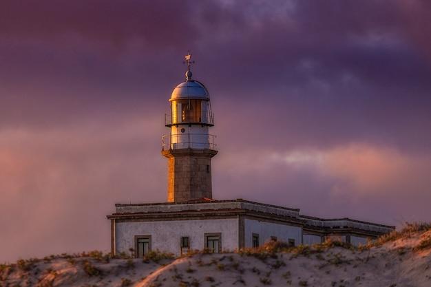 Latarnia larino pod zachmurzonym niebem podczas wieczornego zachodu słońca w hiszpanii