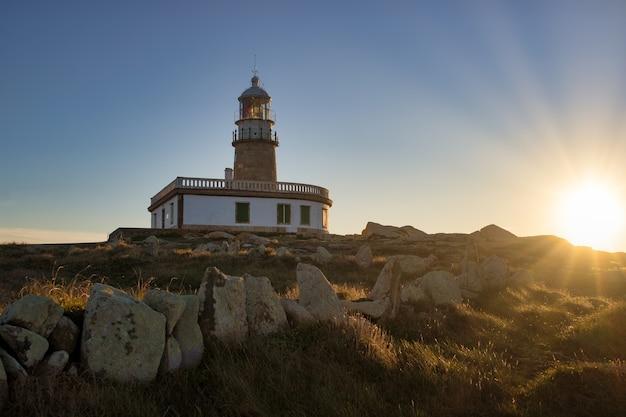Latarnia morska corrubedo otoczona skałami i trawą w słońcu w hiszpanii