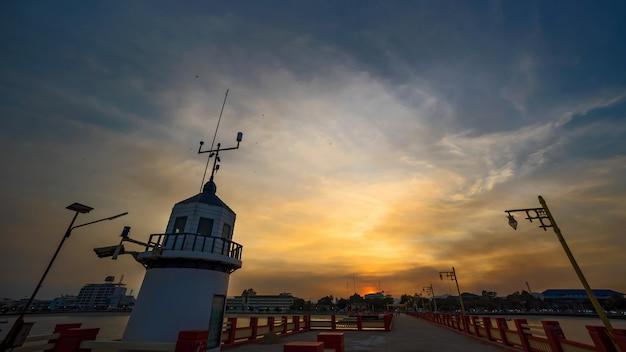 Latarnia morska i molo o zachodzie słońca