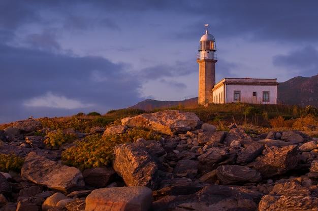 Latarnia morska larino otoczona skałami podczas zachodu słońca w hiszpanii