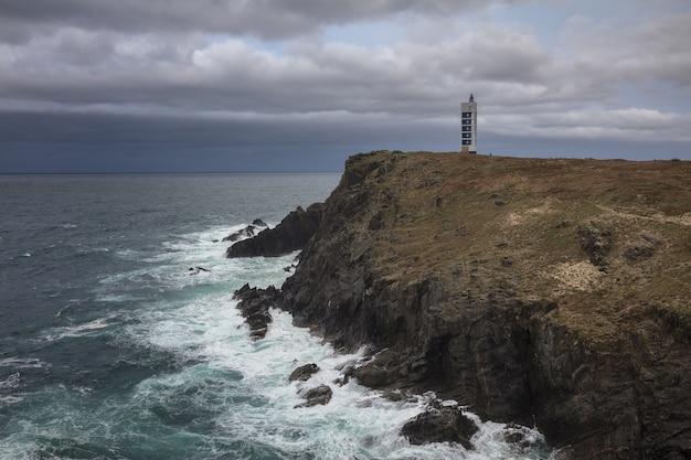 Latarnia morska meiras na klifach valdovino otoczonych morzem pod zachmurzonym niebem w galicji w hiszpanii
