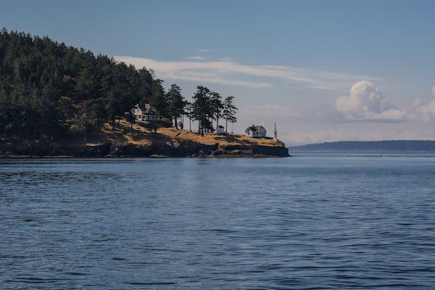 Latarnia morska na brzegu. słońce oświetla las, dom latarnika i brzeg.