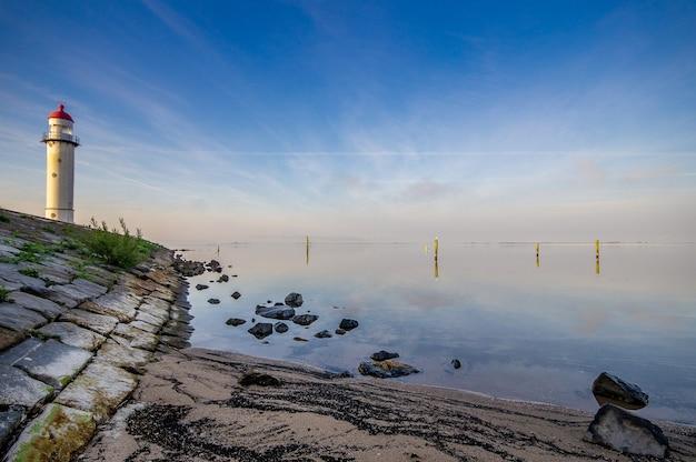 Latarnia morska na brzegu w pobliżu morza z niebieskim pochmurnym niebem