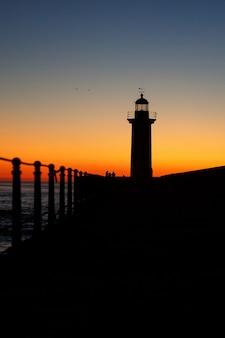 Latarnia morska na ocean sylwetka o zachodzie słońca