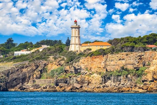Latarnia morska na skalnym klifie i błękitne niebo z chmurami. lizbona, portugalia.