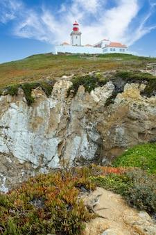 Latarnia morska na szczycie urwiska skalnego i błękitne niebo z chmurami. lizbona, portugalia.