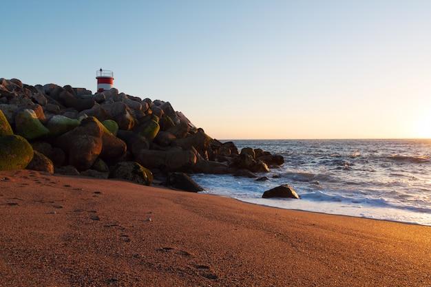 Latarnia morska przy zmierzchem z oceanu wybrzeżem w nazare, portugalia.