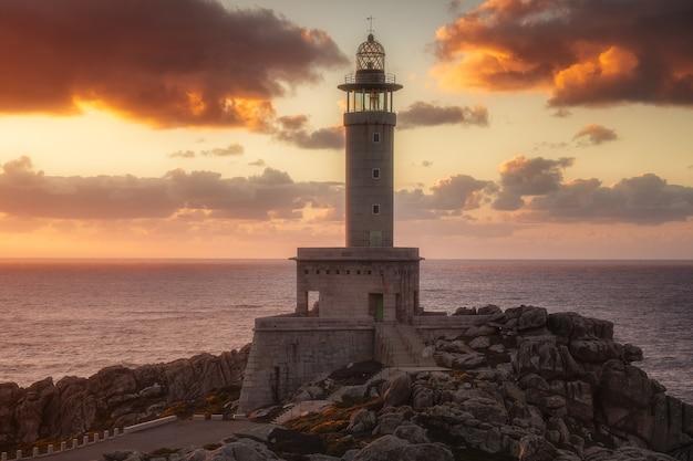Latarnia morska punta nariga w galicji, hiszpania o zachodzie słońca