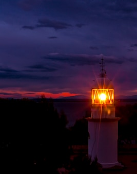 Latarnia morska świecąca w ciemną noc na wybrzeżu hiszpanii