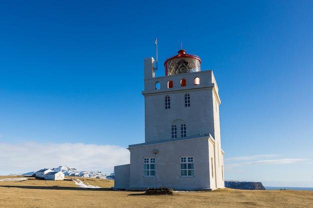Latarnia morska w dyrholaey pod słońcem i błękitne niebo na islandii