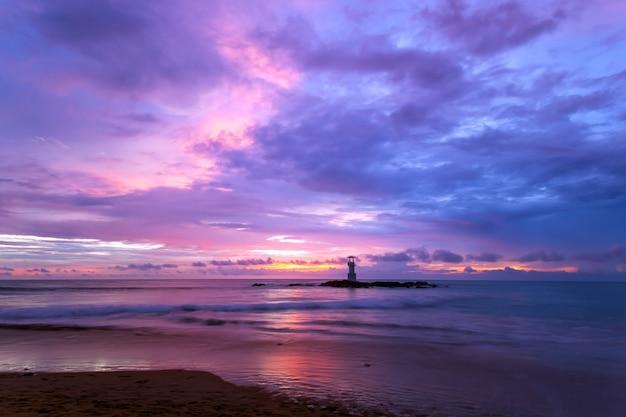 Latarnia morska zachód słońca na skałach na brzegu morza.