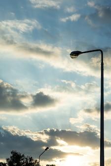 Latarnia na wieczornym niebie z promieniami zachodzącego słońca.