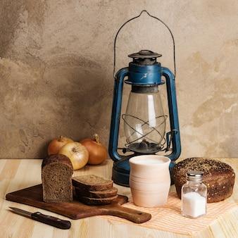 Latarnia naftowa, deska do krojenia, gliniany garnek z mlekiem, chleb żytni, sól i sól, cebula na drewnianym stole